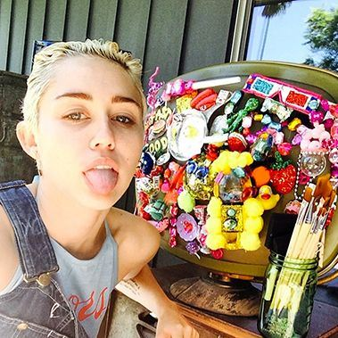 Vacuous popster Miley Cyrus and one of her horrible sculptures